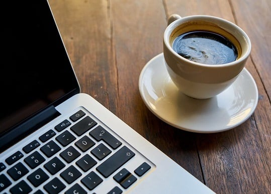 a cup of coffee sat on a desk next to a laptop