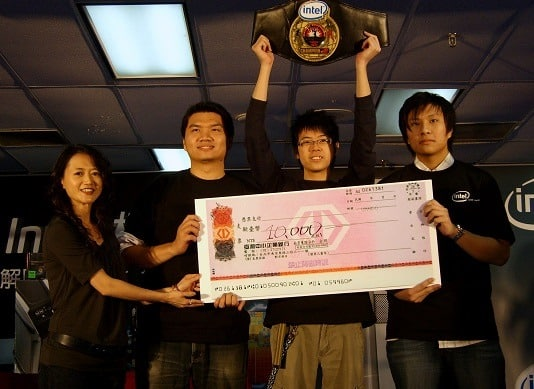 a team a overclocking champions posing with the winners cheque and trophy
