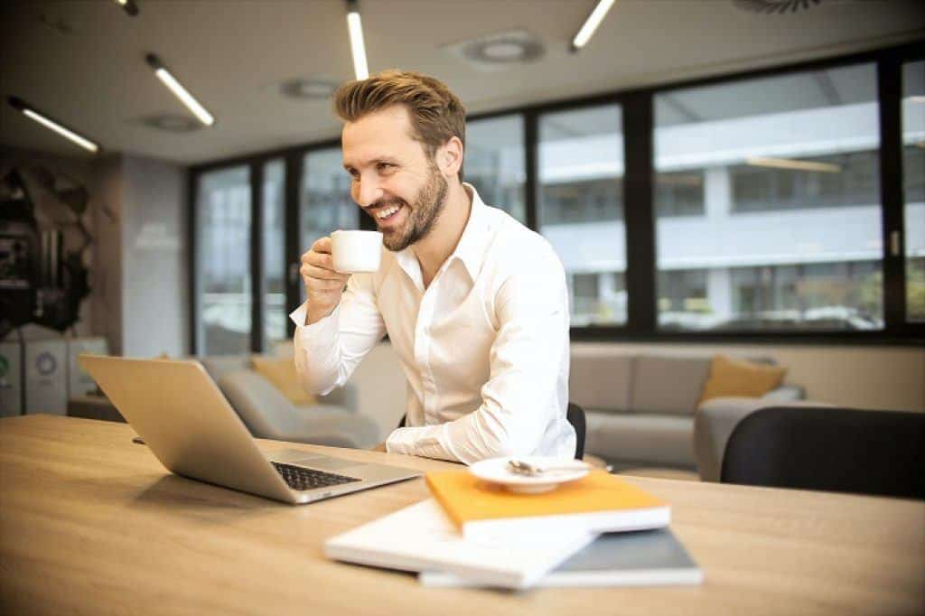 man sitting on a chair while holding a cup in front of laptop