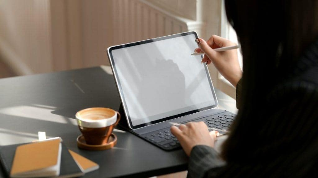 Person using a touchscreen laptop with a stylus pen
