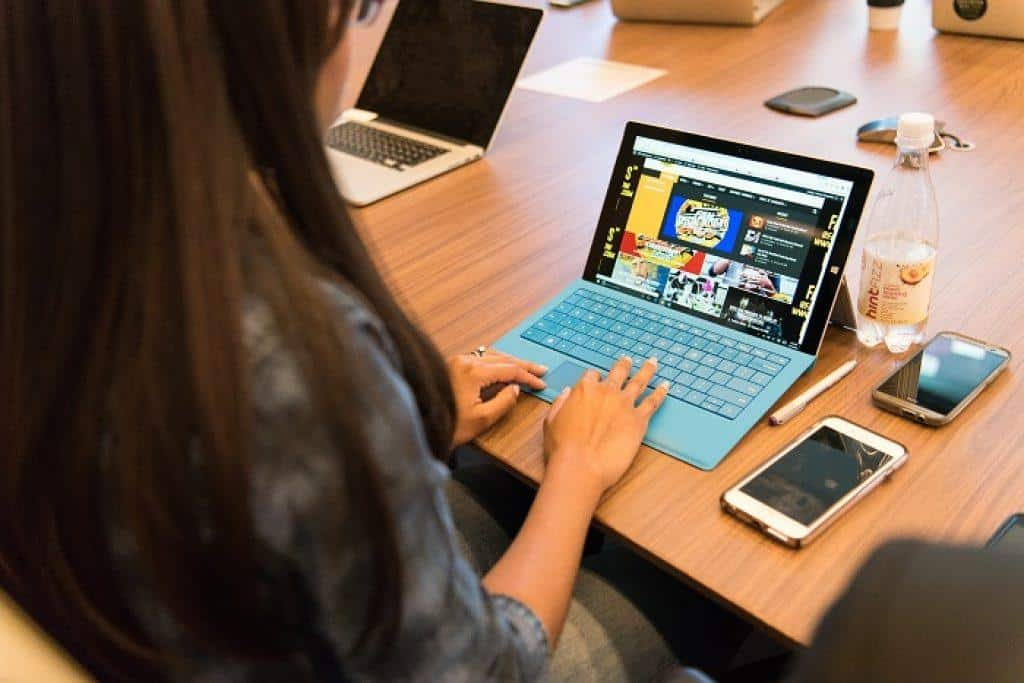 Woman in long sleeved top using a blue laptop