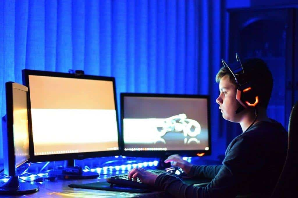 child playing pc games focusing his eyes on one of his multiple monitors