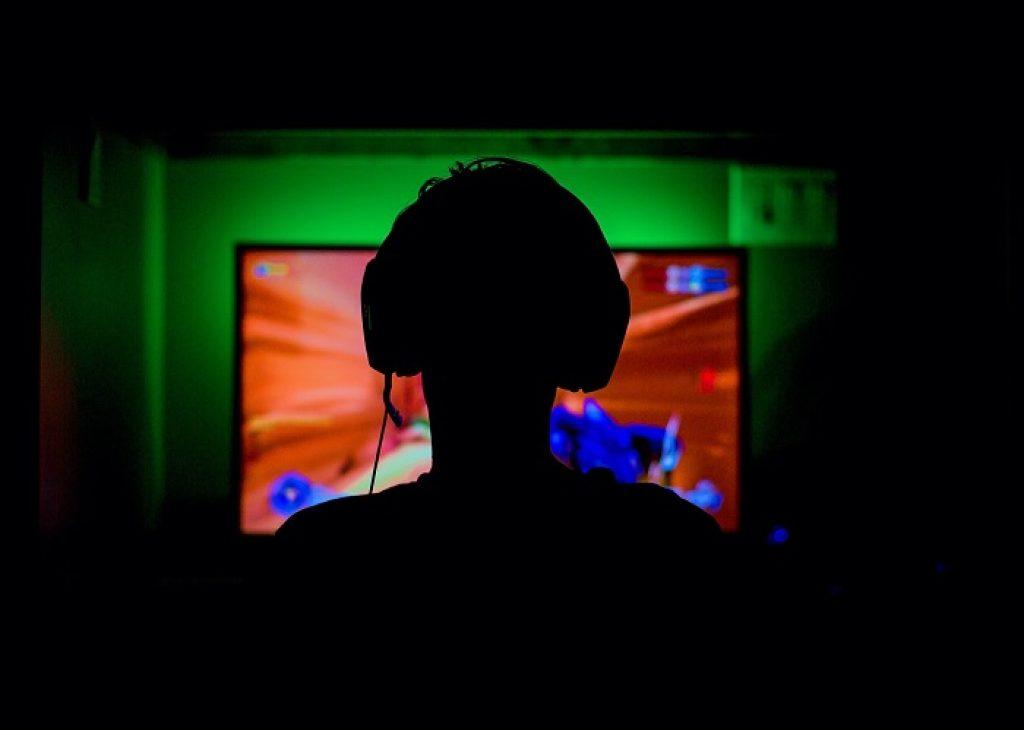 person playing computer game in dark with headphone